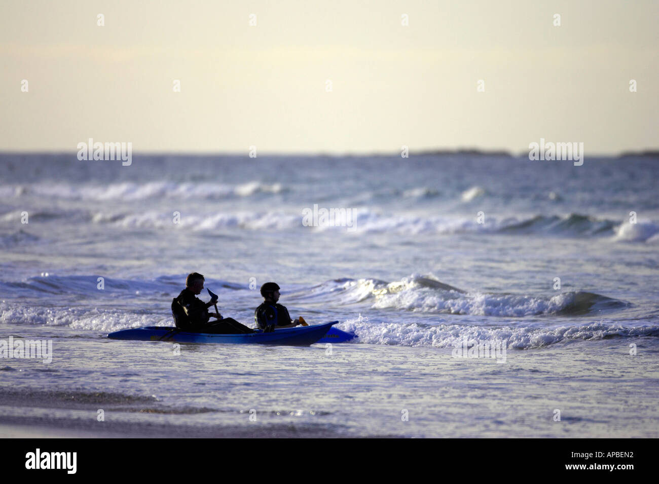two sea kayakers head off the beach into the surf on white rocks beach portrush county antrim northern ireland - Stock Image