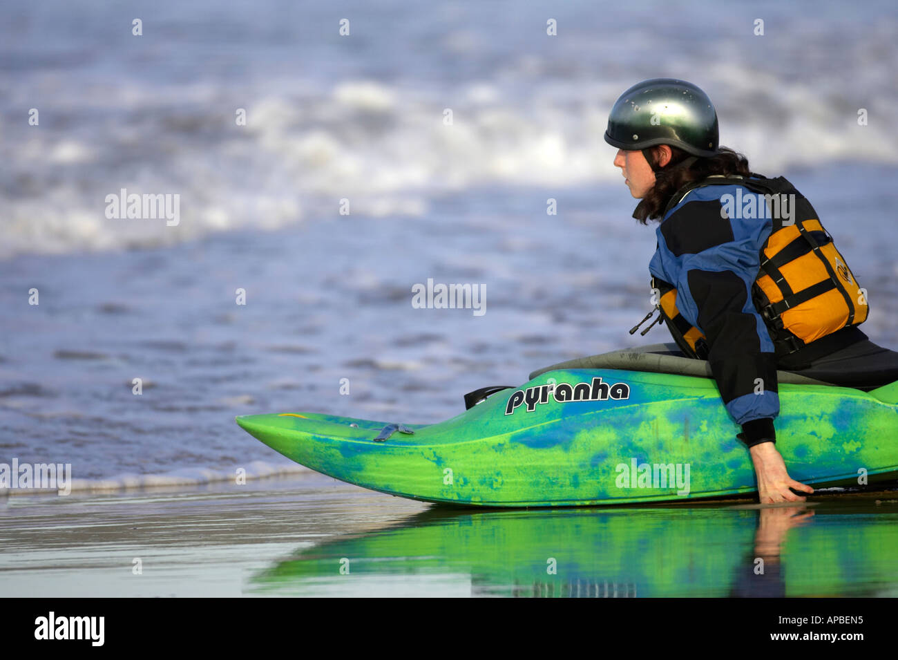 female kayaker pushes her sea kayak off the beach into the water from white rocks beach portrush - Stock Image