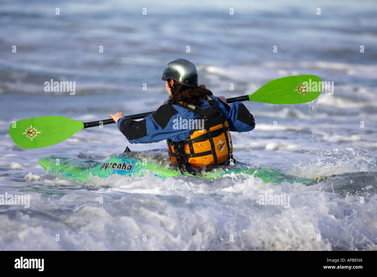 female kayaker paddles out into the surf on white rocks beach portrush county antrim northern ireland - Stock Image
