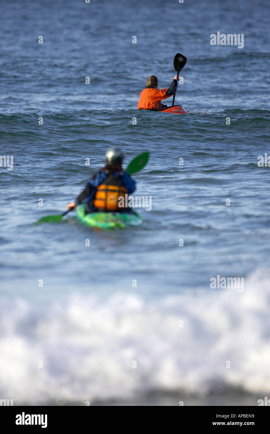 female and male sea kayakers paddle out to sea from white rocks beach portrush county antrim northern ireland - Stock Image