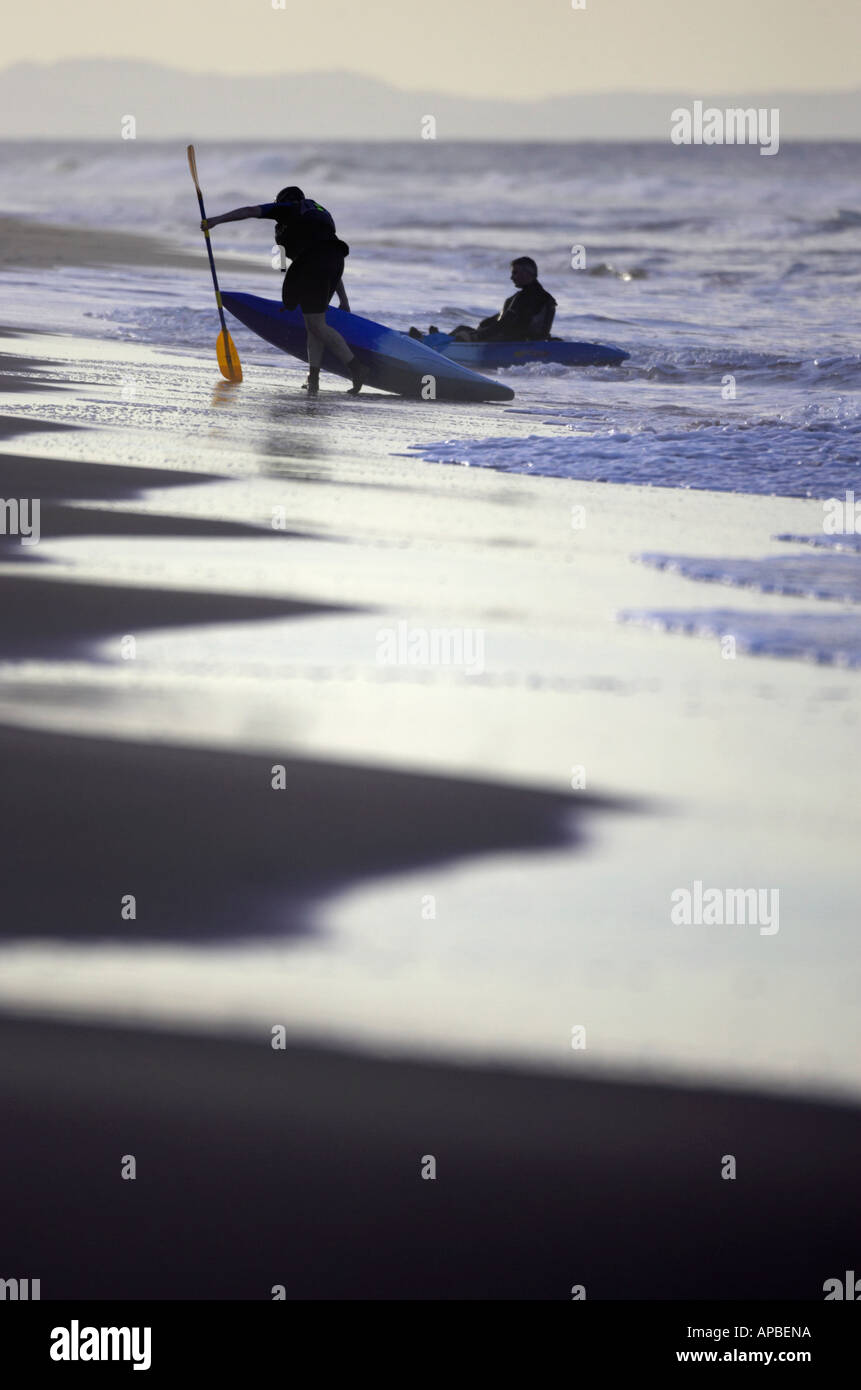 two sea kayakers get out of the sea at the end of the day on white rocks beach portrush county antrim northern ireland - Stock Image