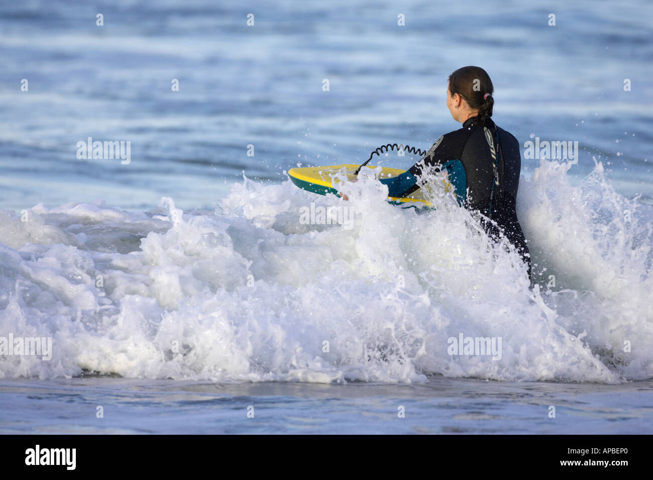 female bodyboarder in wetsuit pushes board into wave off white rocks beach portrush county antrim northern ireland Stock Photo