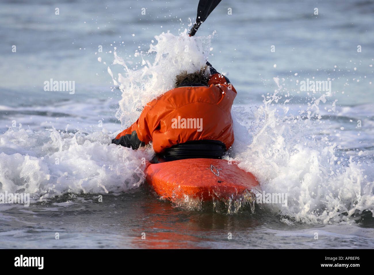 male kayaker hit by a wave paddling out into surf on white rocks beach portrush county antrim northern ireland - Stock Image