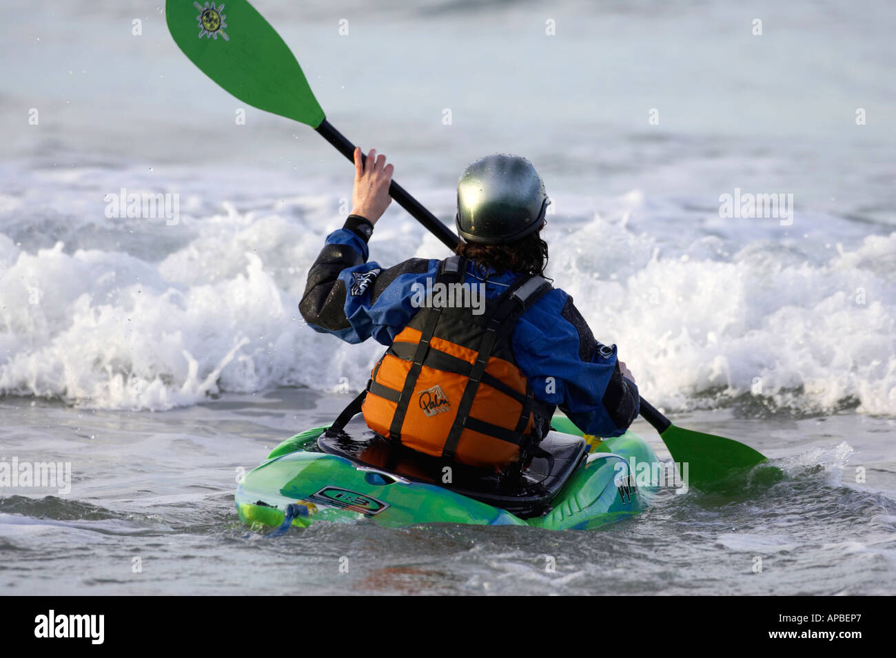 female kayaker paddling out into the waves and surf on white rocks beach portrush county antrim northern ireland - Stock Image