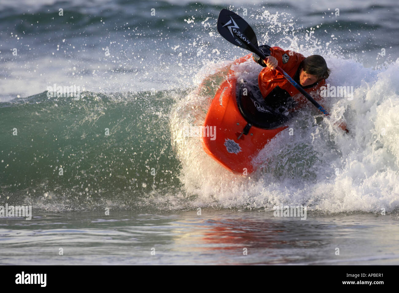 male kayaker rides a wave in the sea off white rocks beach portrush county antrim northern ireland - Stock Image
