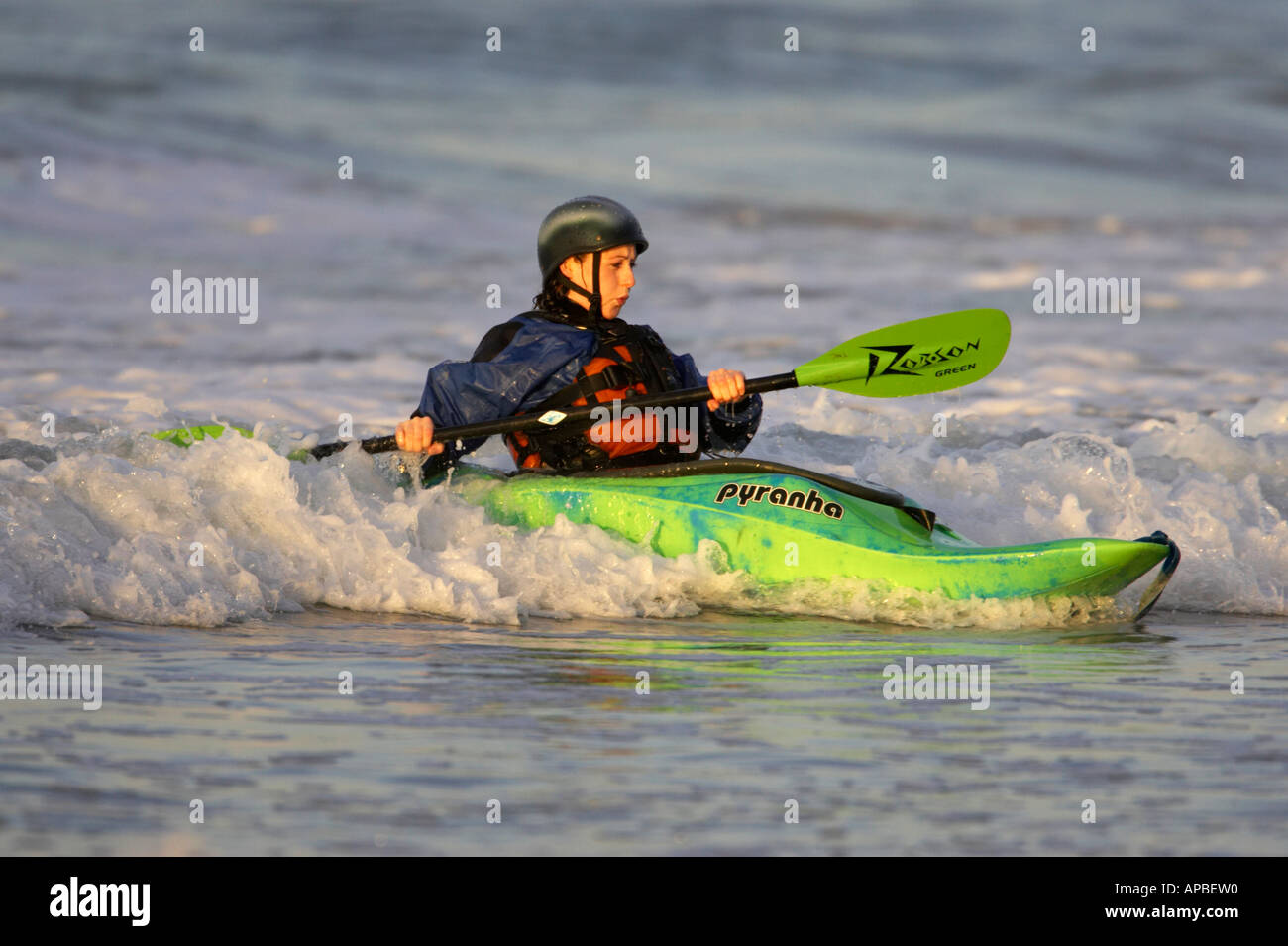 Female kayaker rides a wave off white rocks beach portrush county antrim northern ireland - Stock Image