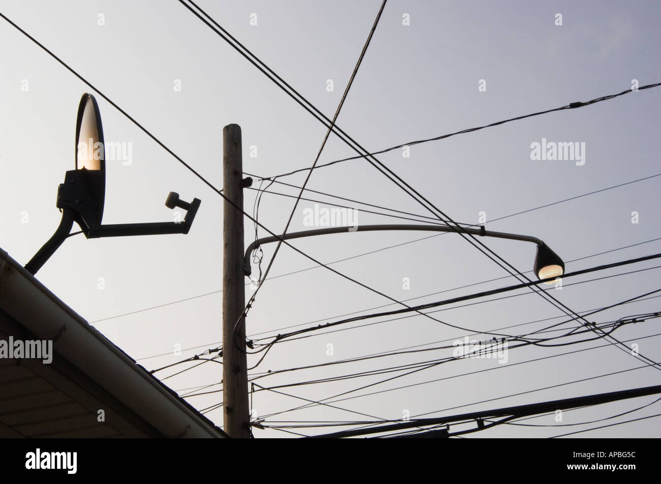 tangle of high wires a street lamp and a satellite TV dish on the ...