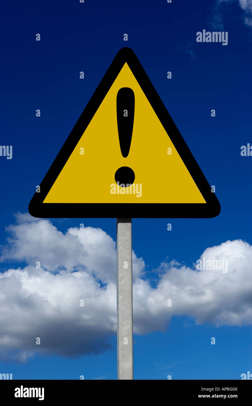 YELLOW TRIANGULAR WARNING SIGN WITH BLACK EXCLAMATION MARK AND BLUE SKY BACKGROUND - Stock Image