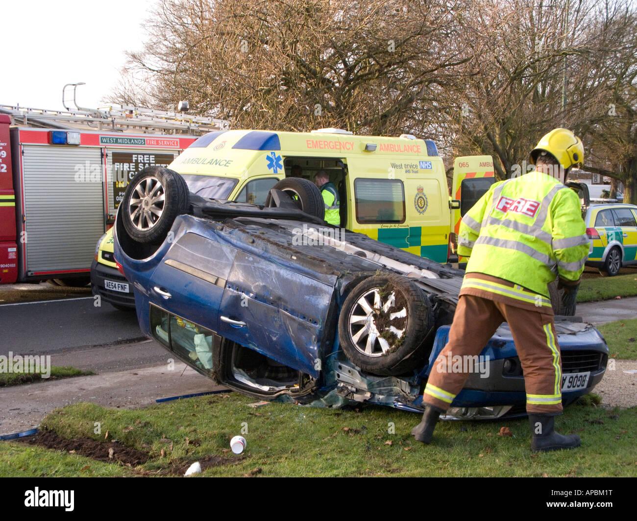 Fireman checks overturned car at road accident scene Stock Photo ...