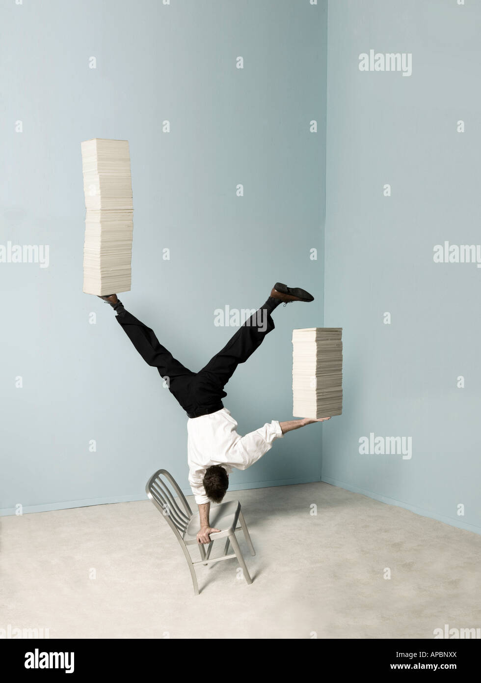 business man balances stacks of papers while doing a handstand on a chair in the office balance multi task - Stock Image