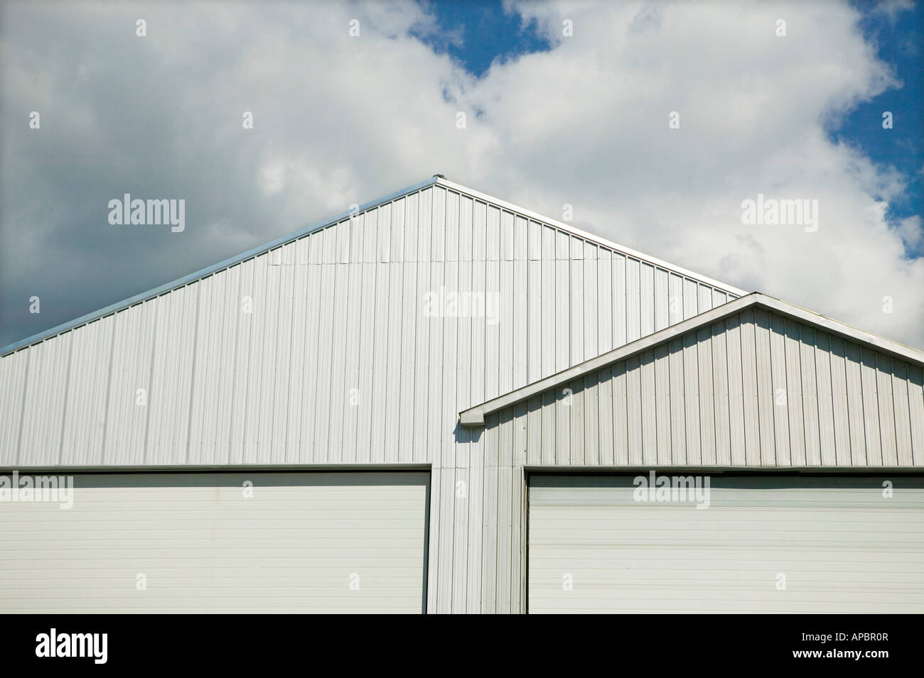 clean white roof lines at angles and triangle pattern with sky and clouds Garage storage facility under the roof - Stock Image