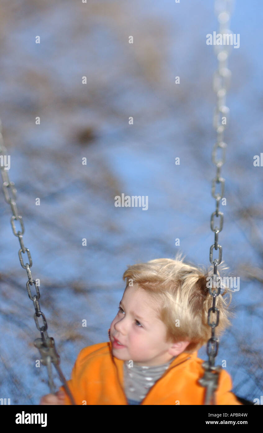 caucasian boy age 5-6 swings on swing with blue sky and trees and shallow focus orange sweater - Stock Image