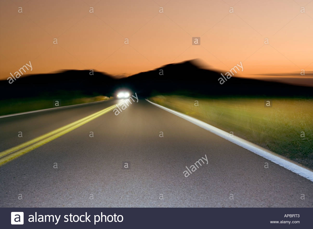 Driving on desert highway at night, dusk, west of  Tucson Arizona Drivers point of View oncoming traffic car headlights - Stock Image