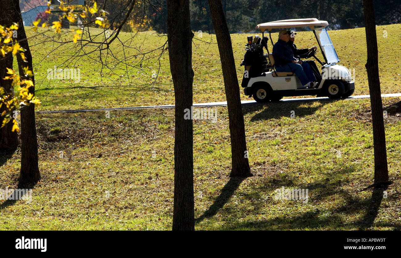 Golfers advance to a tee box in their golf cart at Berksdale Golf Course in Bella Vista, Ark. - Stock Image