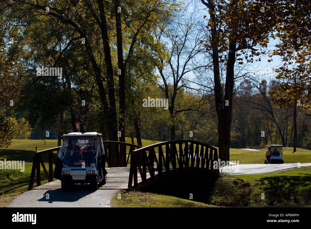 Golfers make their way along a path in their golf cart at Kingswood Golf Cart in Bella Vista, Ark. Stock Photo