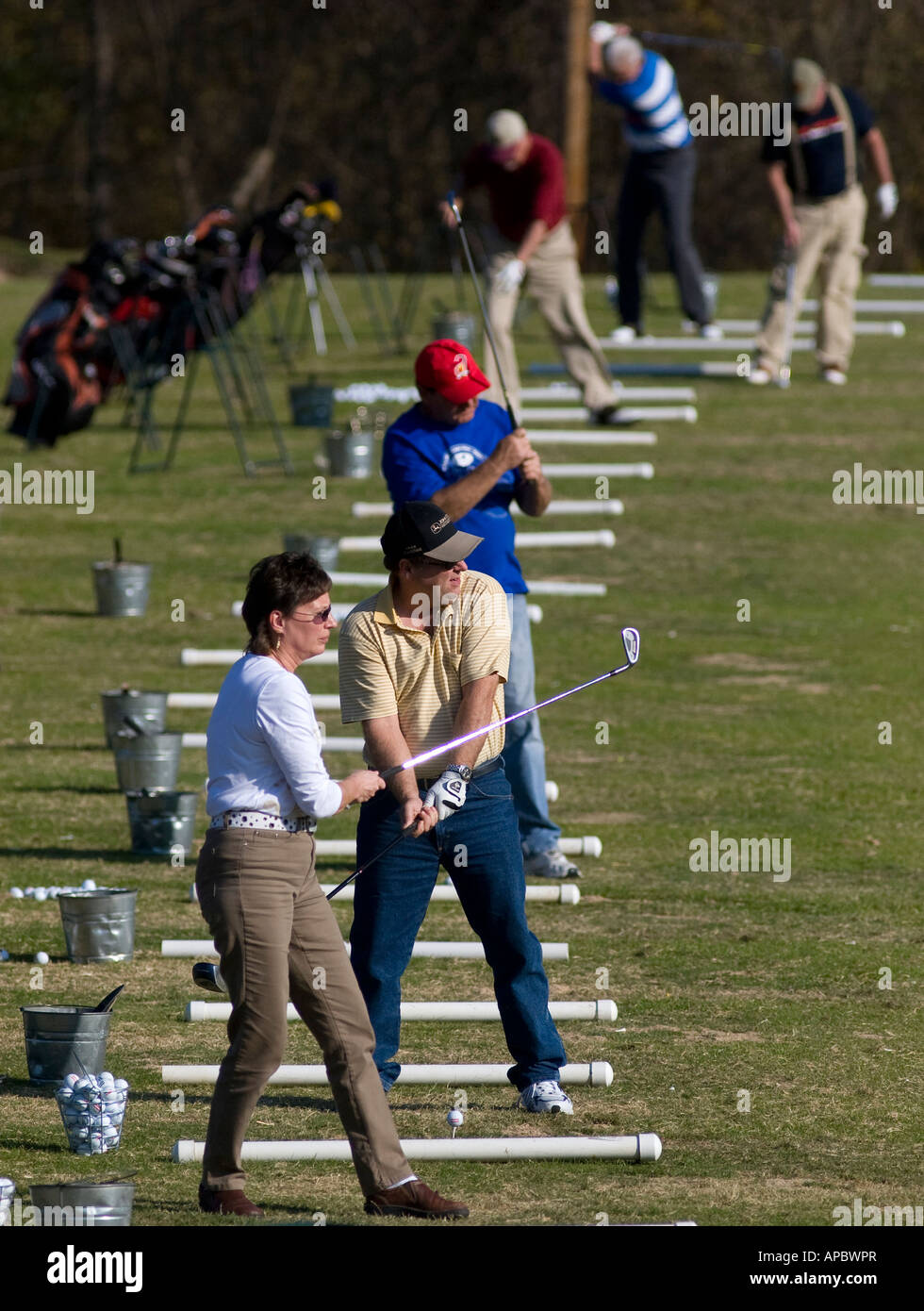 Golfers practice their strokes on the driving range at Tanyard Creek in Bella Vista, Ark. Stock Photo
