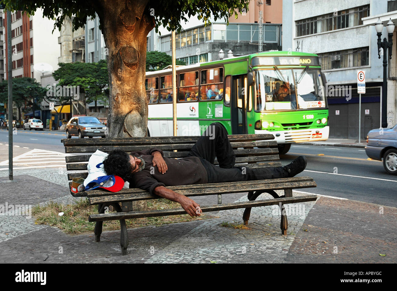 Homeless man sleeping on a bench in the center of Sao Paulo, Brazil Stock Photo