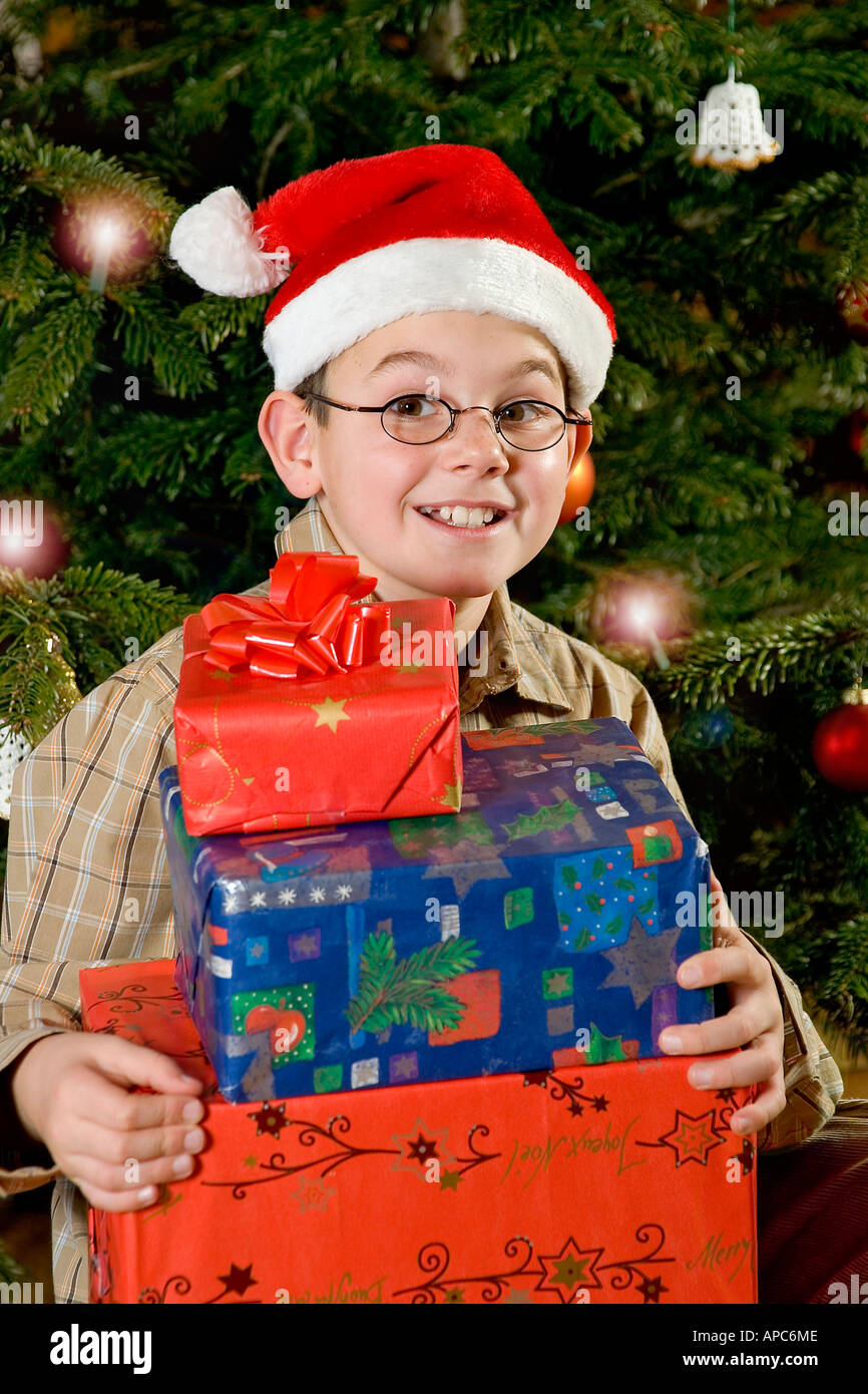 A ten years old boy with Christmas presents on Christmas Eve - Stock Image