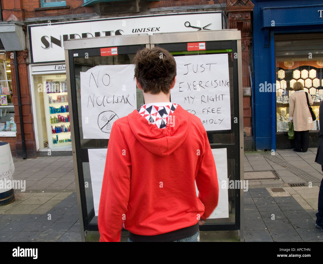 young man looking at home made protest banners calling for free speech and no bombs pasted on telephone boxes Aberystwyth - Stock Image