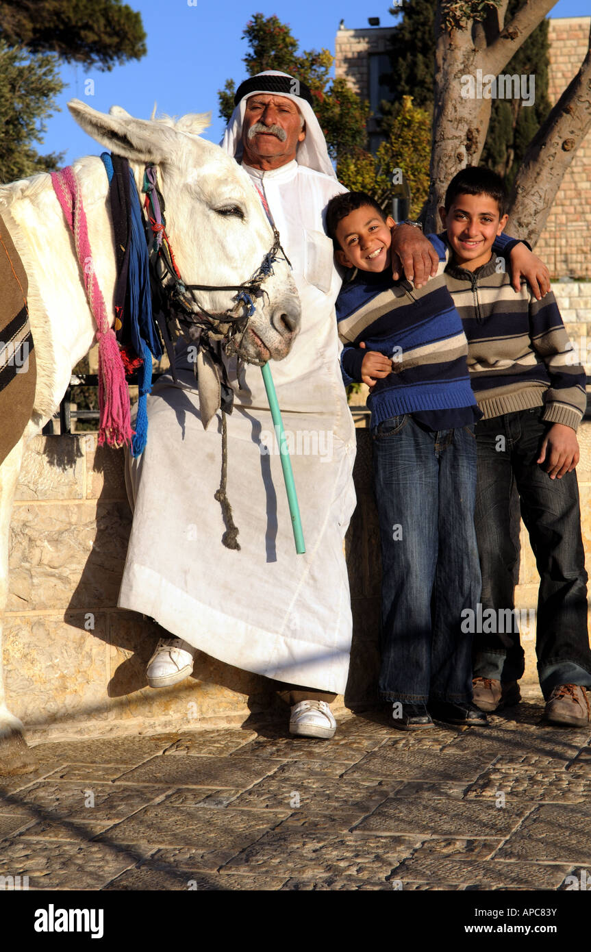 A family portrait- Standing with their donkey On the beautiful Mt of olives promenade in Jerusalem. Stock Photo