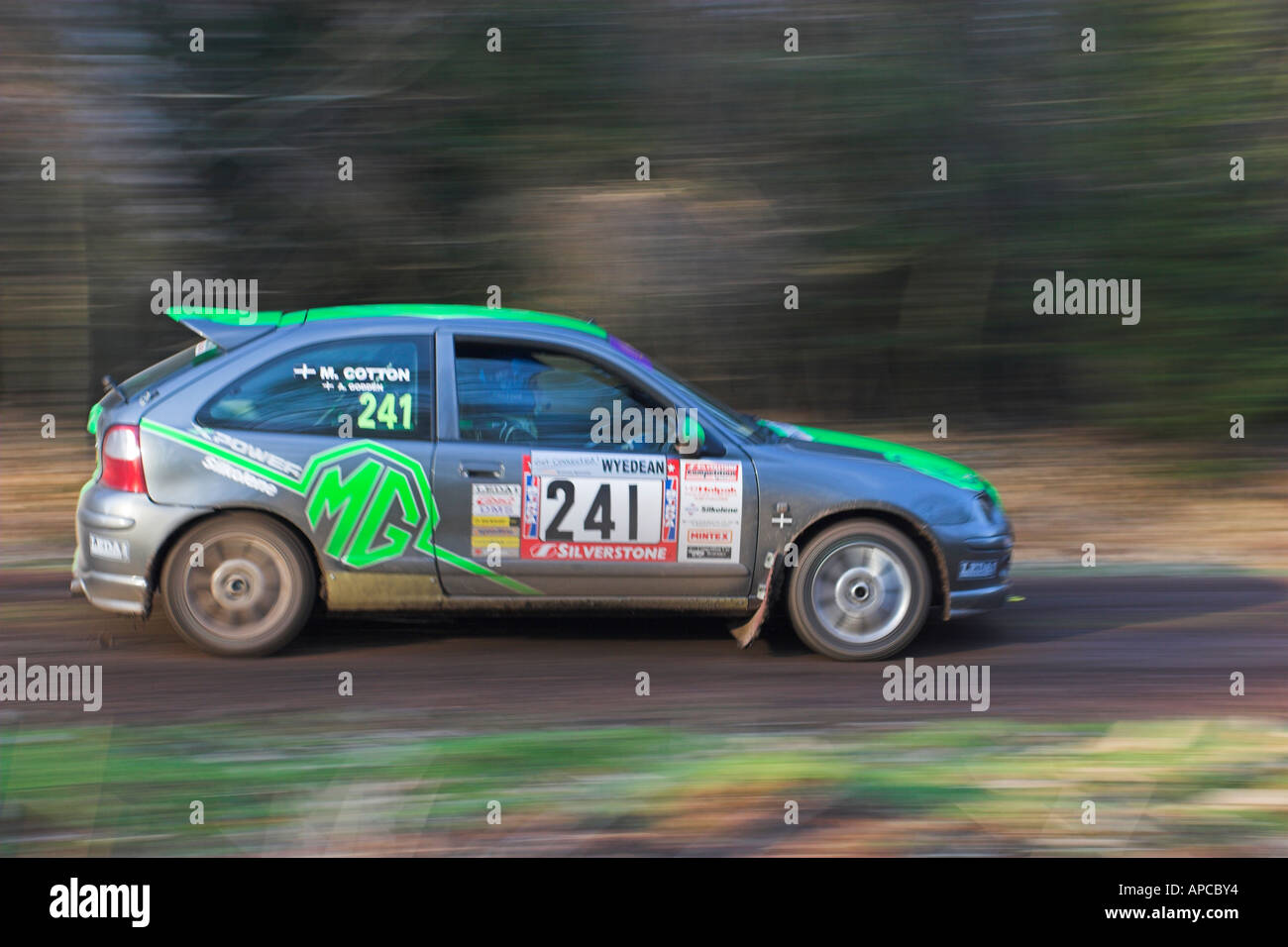 Silver and green rally car against blurred background and foreground ...