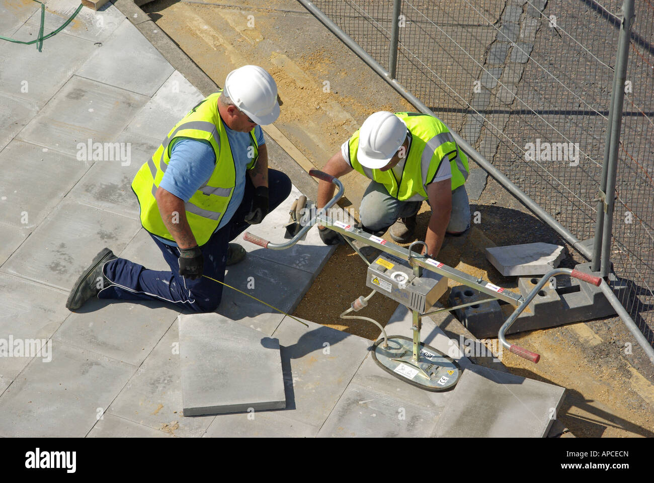 London pavement relaying work in progress two workmen kneeling beside slab lifting tool - Stock Image
