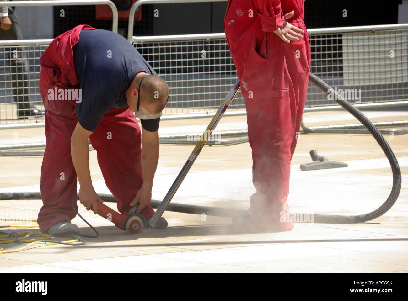 City of London pavement repair work in progress two workmen using disc cutter vacuum dust control - Stock Image
