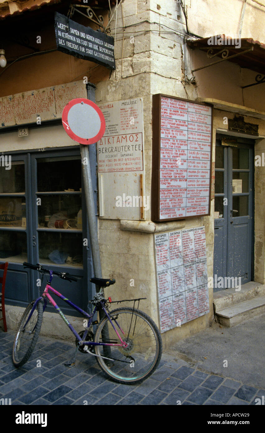 Bicycle locked to post with signs in Greek language Rethimnon Crete Europe - Stock Image