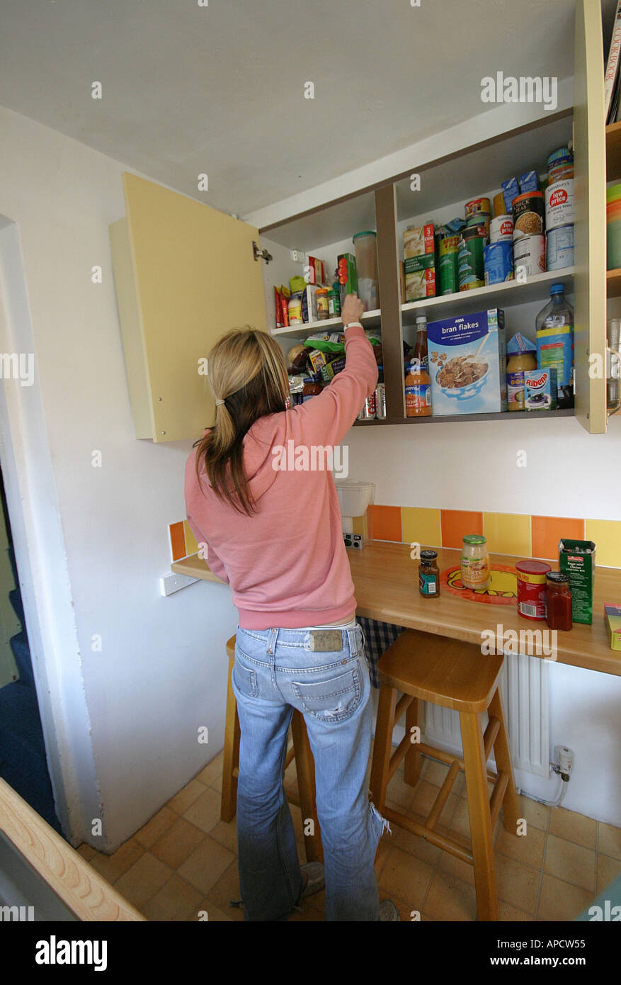 a student girls looking for food in a cupboard in a student house Stock Photo