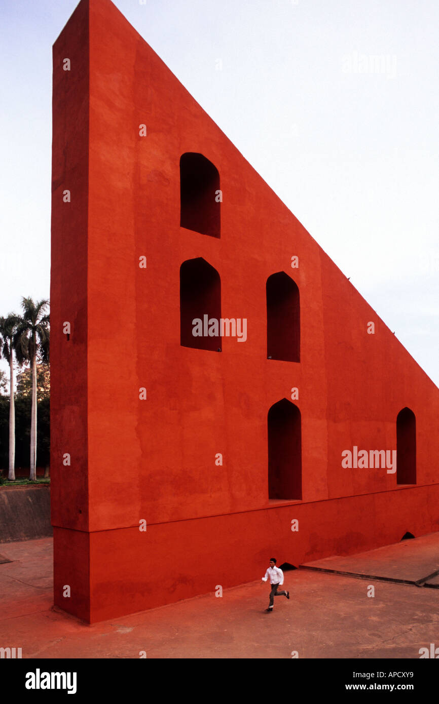 A samll boy runs past the giant sundial, Samrat Yantra at Jantar Mantar ancient observatory in Delhi, India - Stock Image
