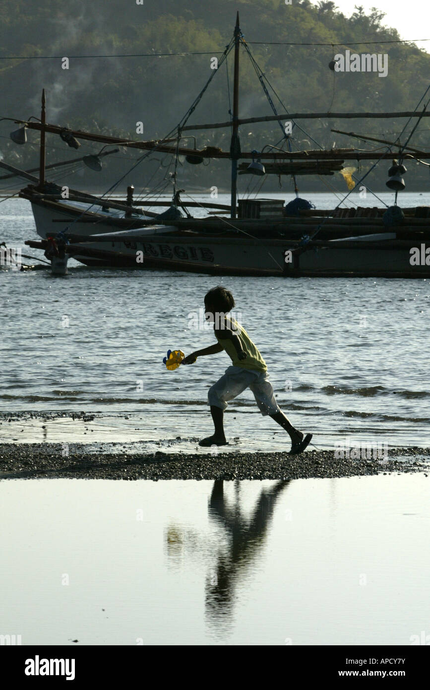 A child plays on the beach in the early morning in Mansalay, Oriental Mindoro, Philippines. Stock Photo