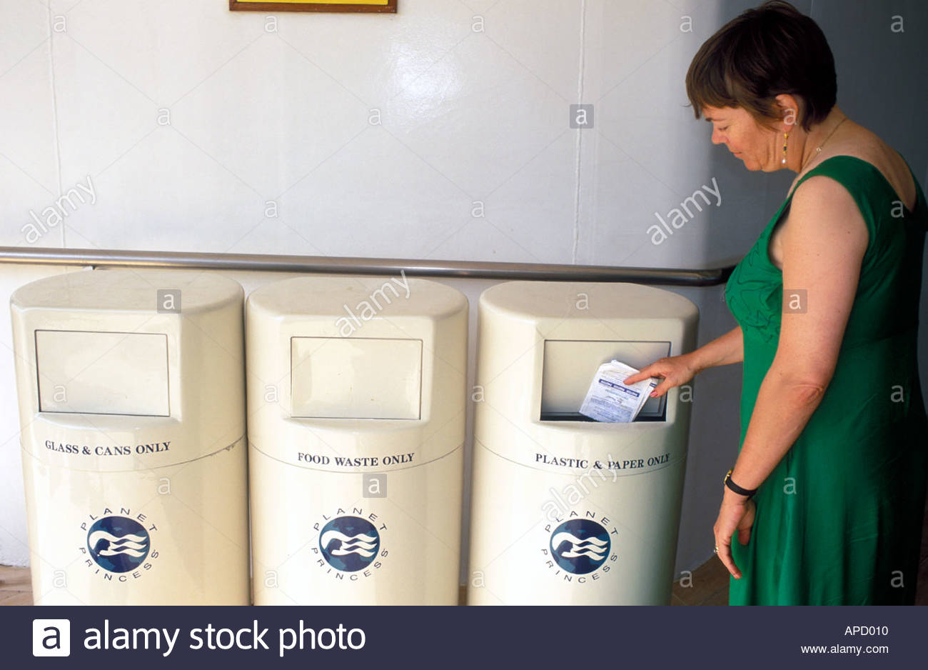 Woman using differentiated recycling bins on cruise ship UK - Stock Image