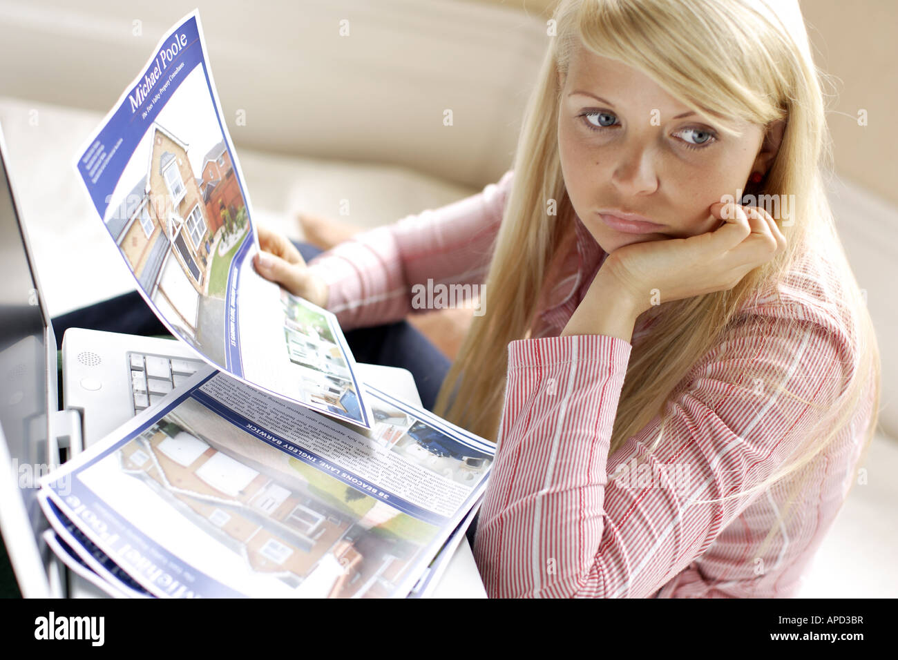 young woman looking at particulars for houses and flats - Stock Image