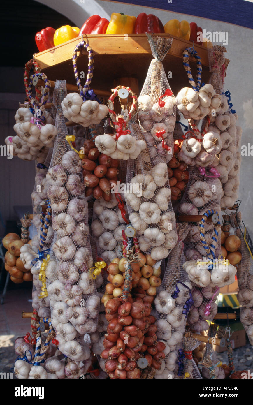 Strings and bunches of white garlic tempt buyers at a garlic festival in Saint Clar in southwest France - Stock Image