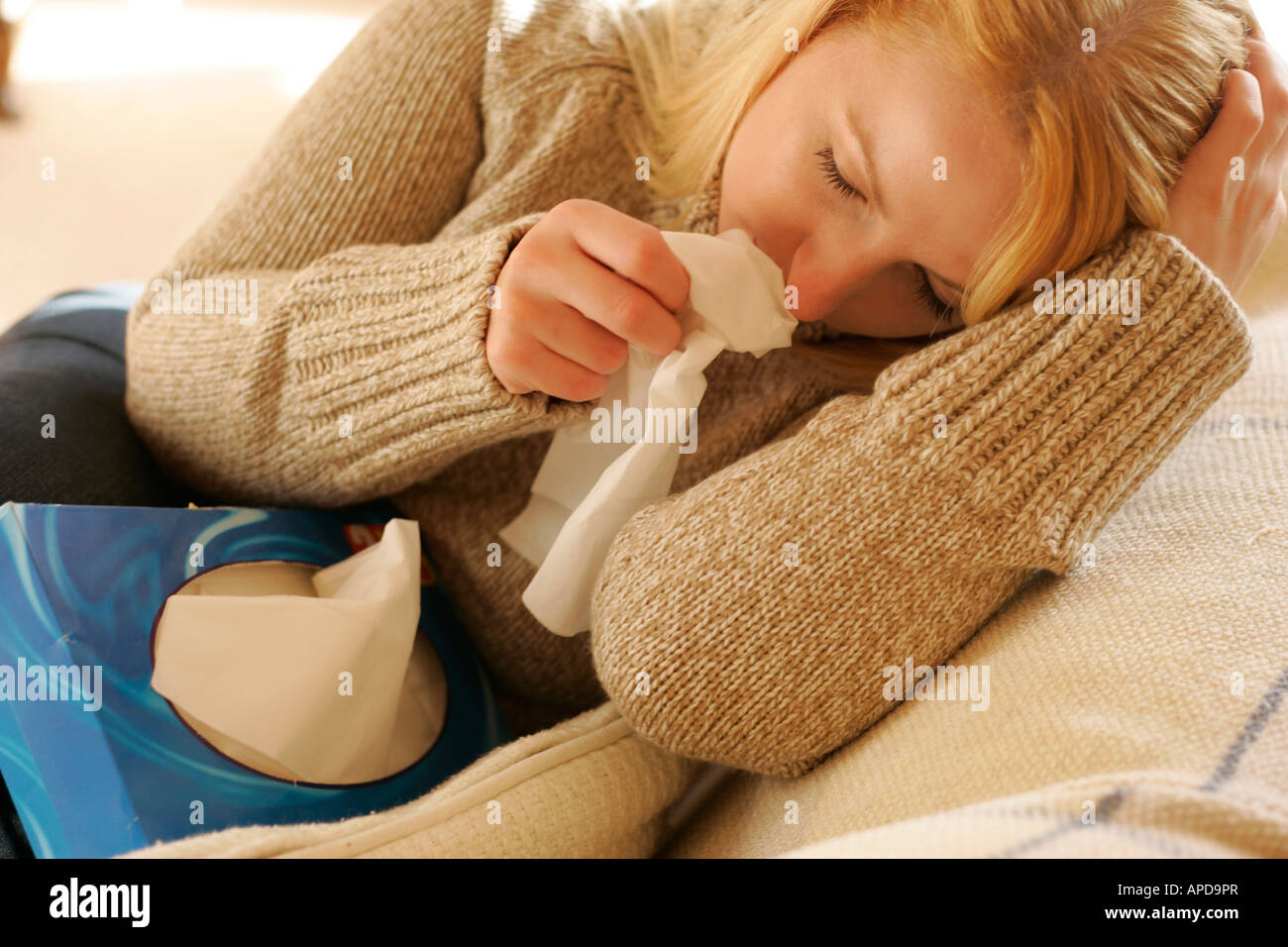 woman with cold and box of tissues - Stock Image