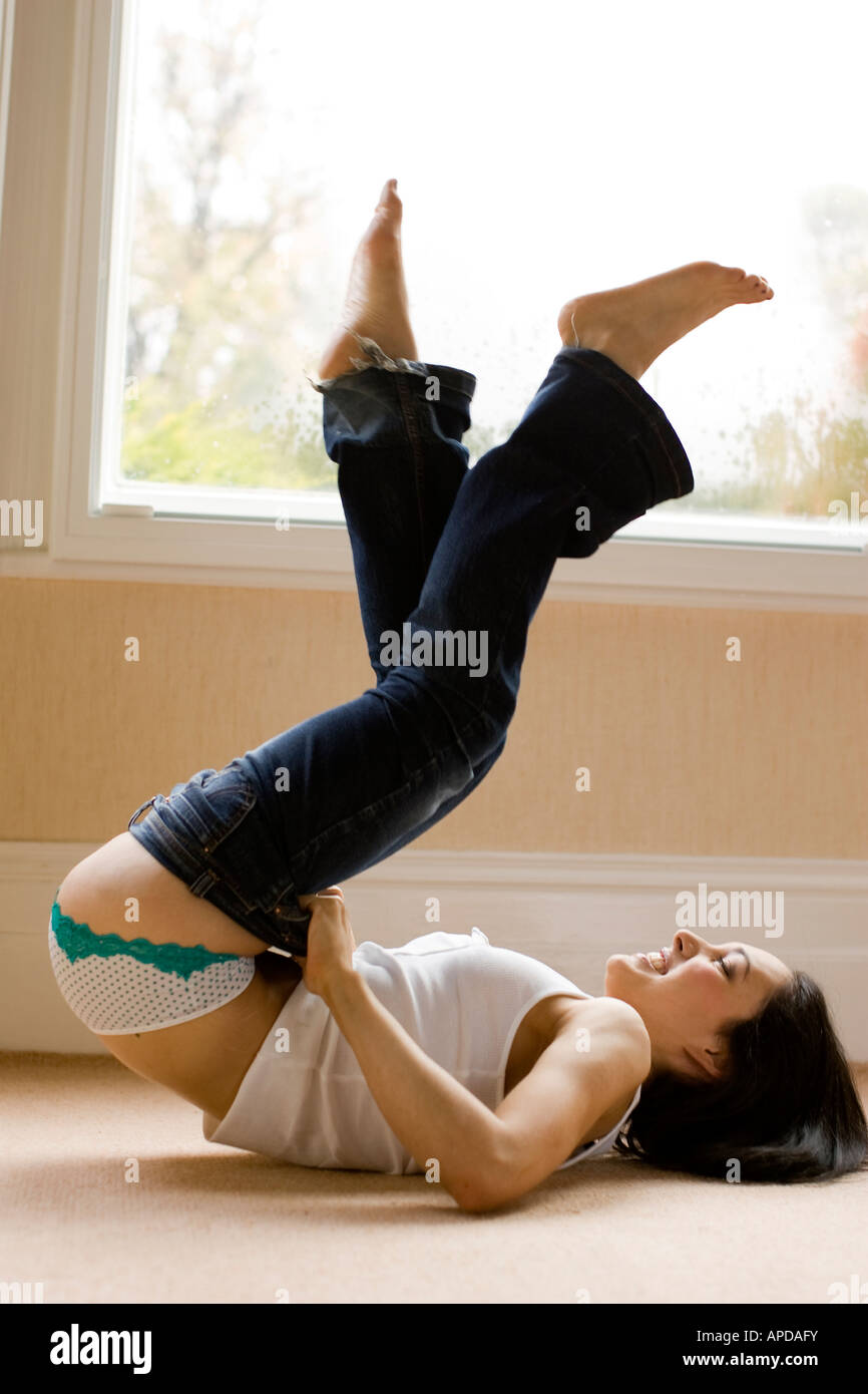 woman putting on tight jeans - Stock Image