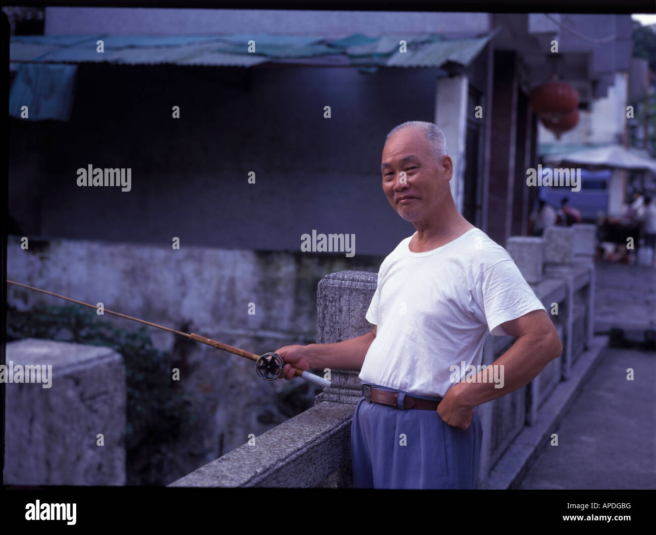 463efd7198c Old Chinese man fishing off a bridge in Yangshuo