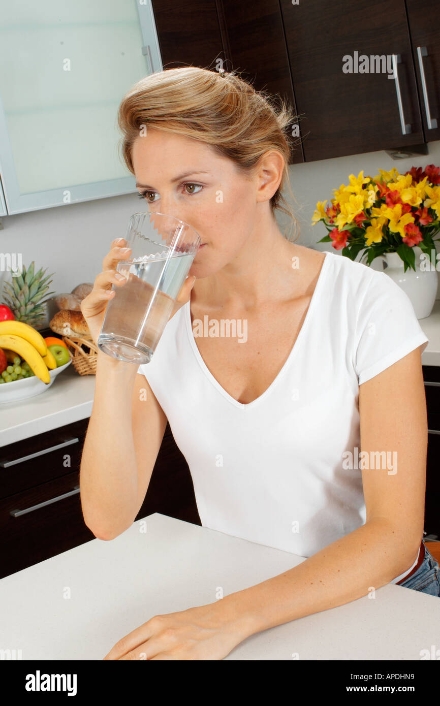 WOMAN IN KITCHEN DRINKING WATER - Stock Image