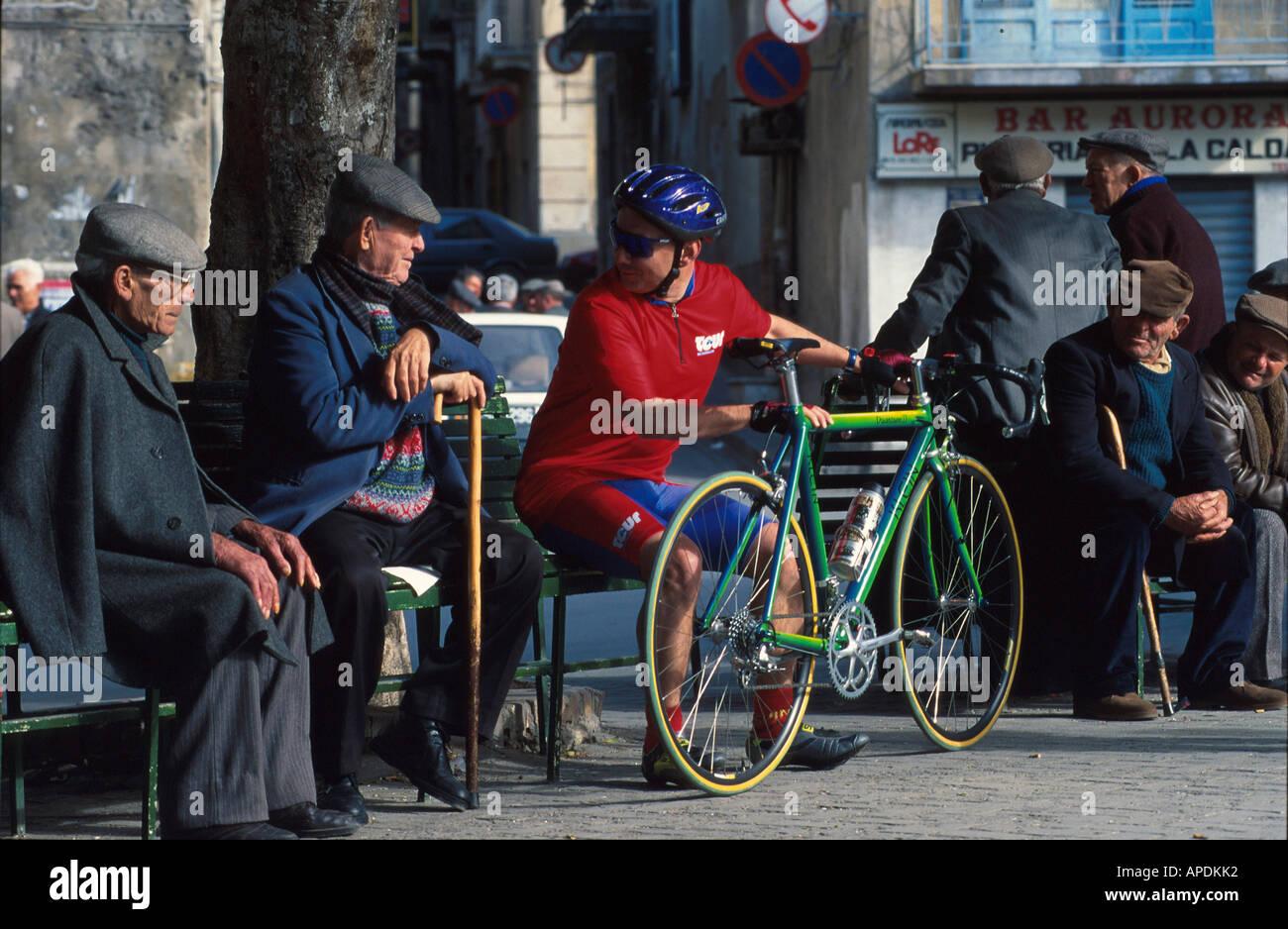 Radfahrer und alte sizilianische Maenner, Piazza von Regalbuto Sizilien, Italien - Stock Image