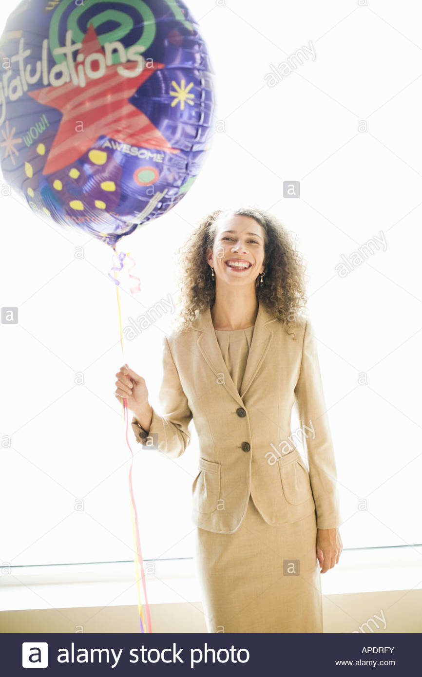 African businesswoman holding balloons - Stock Image