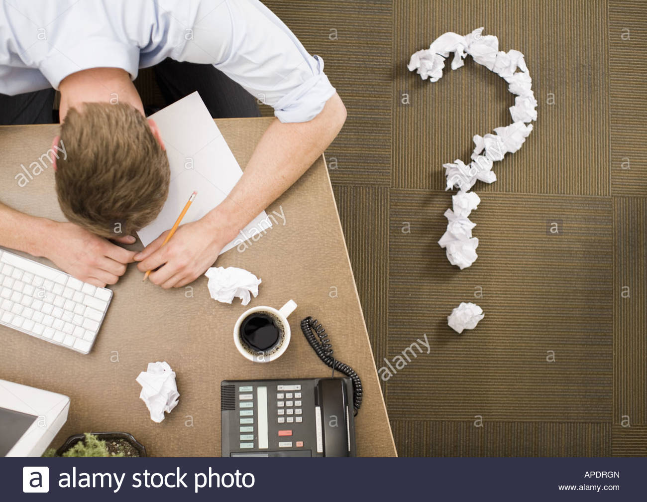 Businessman next to crumpled paper question mark - Stock Image