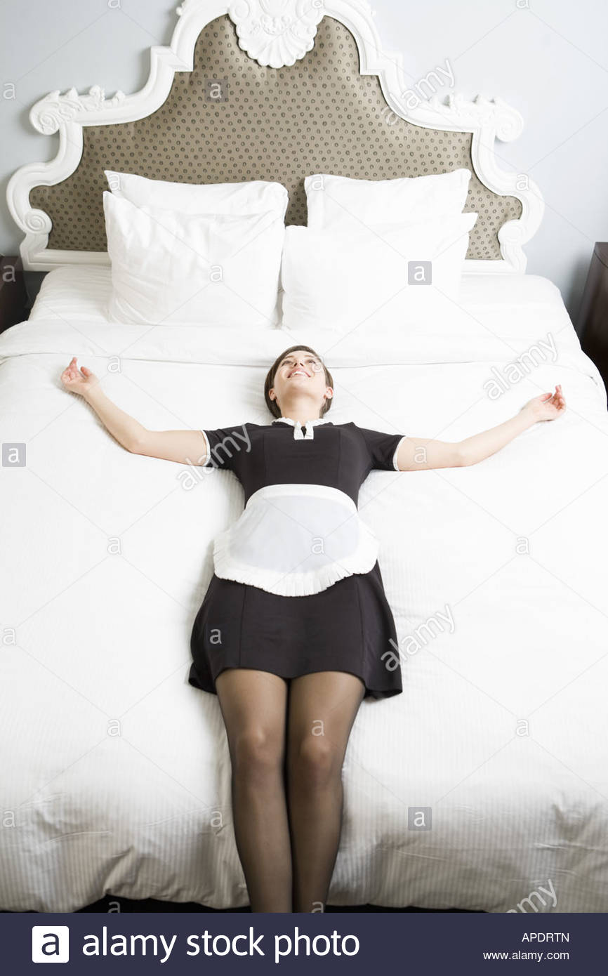 Maid laying on bed - Stock Image