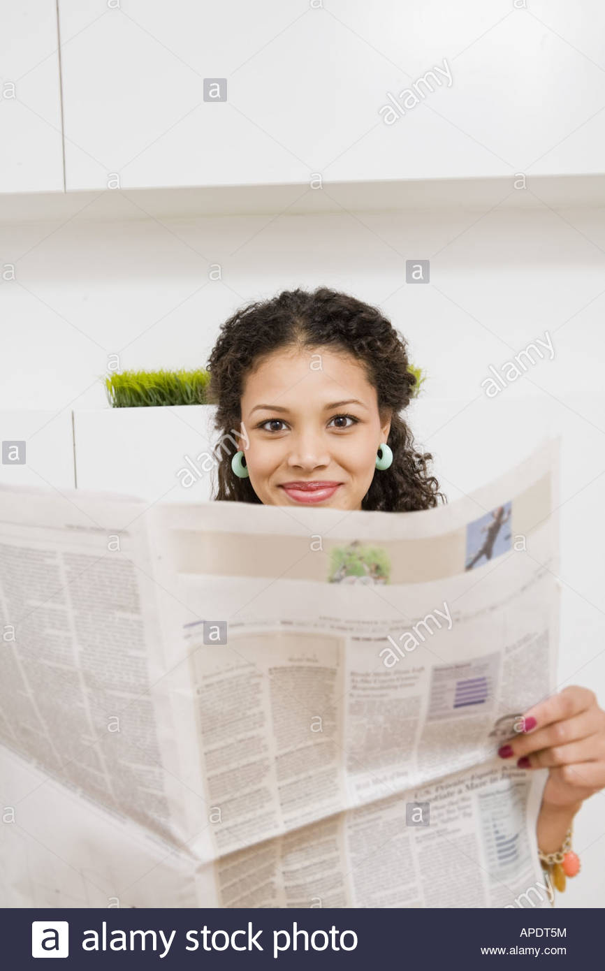 African woman holding newspaper - Stock Image