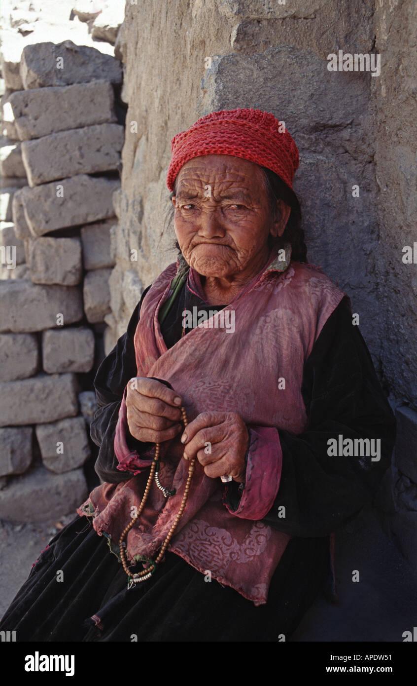 Elderly Ladakhi woman seated knitting Leh Jammu and Kashmir northern India - Stock Image