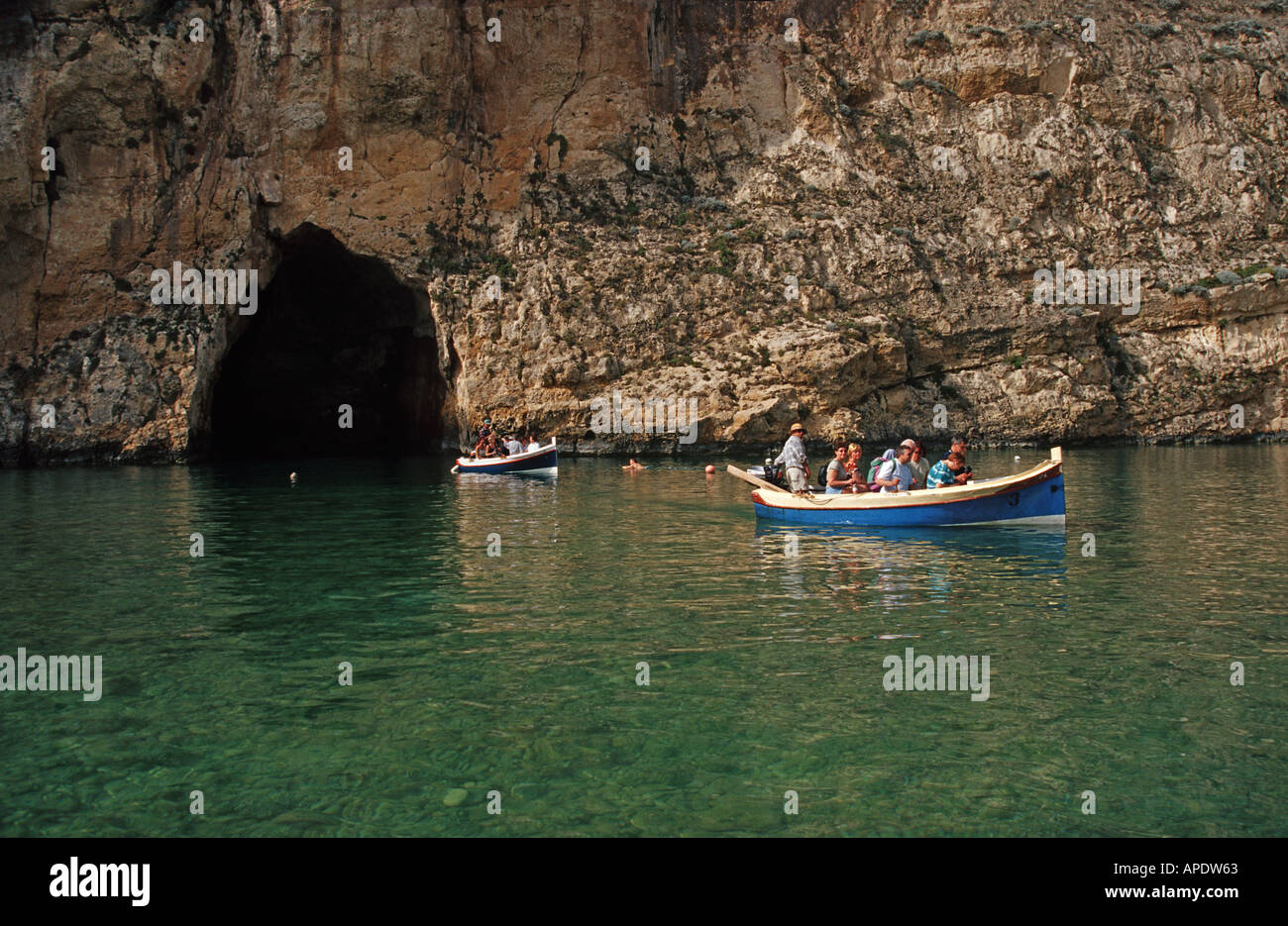 Boat carrying tourists through the narrow tunnel which separates the Inland Sea to the Mediterranean sea Dwejra Point Gozo Malta - Stock Image