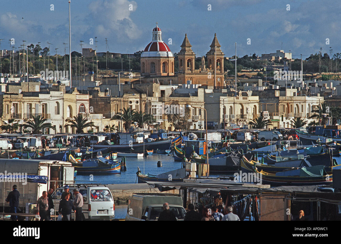 Traditional Maltese fishing boats called Luzzus moored in Marsaxlokk harbour Our Lady of Pompeii church in the background Malta - Stock Image