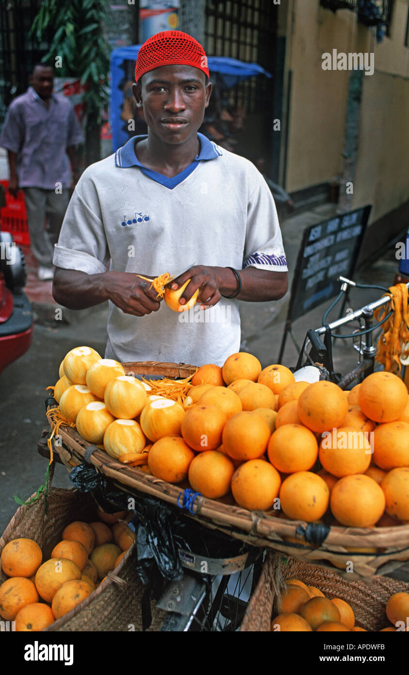 Itinerant vendor selling oranges from the baskets attached to his bicycle Dar es Salaam Tanzania East Africa - Stock Image