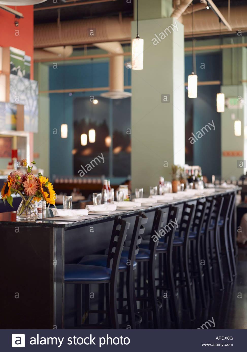 Place settings and stools at bar - Stock Image