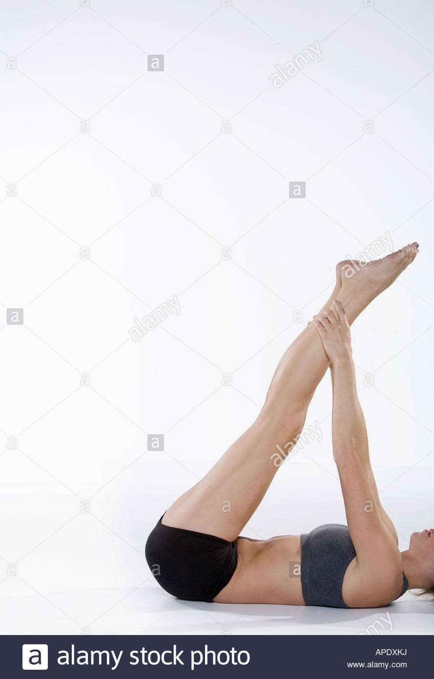 Woman in athletic gear stretching - Stock Image