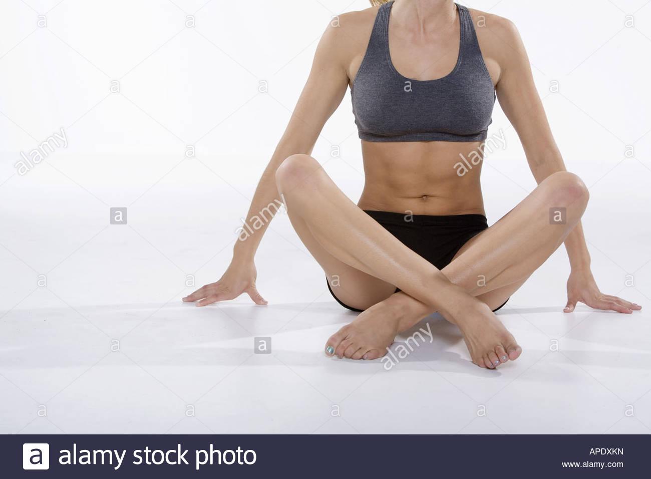 Woman in athletic gear sitting cross-legged - Stock Image